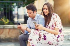 Young couple dating in the park and using smartphones. Picture of young couple dating in the park in summer royalty free stock photography