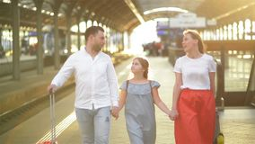 Young Couple with Daughter Arrivals From Vacations. Family Walking On Platform of Railway Station With Suitcases. Happy stock video footage