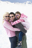 Young couple and daughter (7-9) wearing sunglasses in snow field, man carrying daughter on back, smiling, portrait Royalty Free Stock Photo