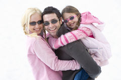 Young couple and daughter (7-9) wearing sunglasses in snow field, man carrying daughter on back, smiling, portrait Stock Image