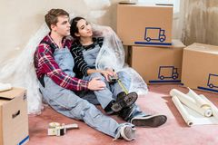 Young couple day dreaming about their future after moving in. Happy young couple wearing overalls while resting and day dreaming about their future together Stock Images
