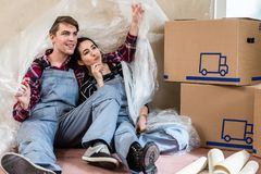 Young couple day dreaming about their future after moving in new home. Happy young couple wearing overalls while resting and day dreaming about their future Stock Photography