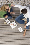 Young couple on decking, man feeding woman sushi with chopsticks, elevated view Stock Image