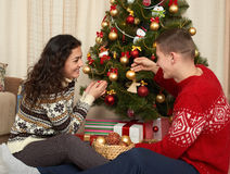 Young couple decorate christmas fir tree. Home interior with gifts. New year holiday concept. Love and tenderness. Royalty Free Stock Photo