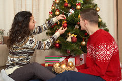 Young couple decorate christmas fir tree. Home interior with gifts. New year holiday concept. Love and tenderness. Stock Image