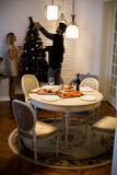 Young couple decorate fir-tree for holidays of Christmas and New Stock Images