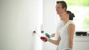 Young couple decorate their new apartment.They are painting the wall. HD stock video