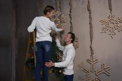 A young couple decorates a house for Christmas with garlands of. A young women is standing on a stepladder and decorating a house for Christmas, and a men Royalty Free Stock Photos