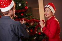 Young couple decorating christmas tree Royalty Free Stock Images