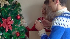 Young couple decorating Christmas tree at home. People wearing winter sweaters stock footage