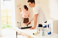 Young couple decorating a room in their house Stock Photography