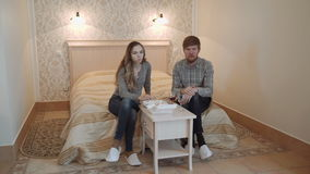A young couple in a deluxe hotel room eat sushi from a lunchbox and drink red wine. stock video