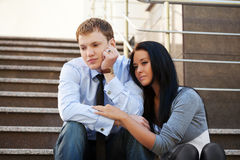 Sad young couple in depression sitting on the steps Stock Photo