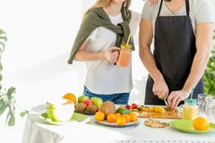 Young couple dicing fruit in the kitchen. Close up cropped photo royalty free stock photo
