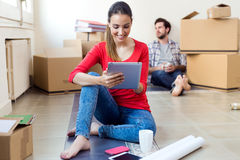 Young couple with digital tablet resting in their new home. Young couple resting during the move to their new home Royalty Free Stock Images