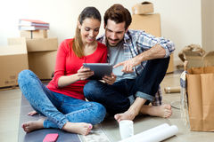 Young couple with digital tablet in their new home Royalty Free Stock Images