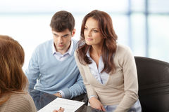 Young couple discussing financial plan with consultat. Contemporary young couple get financial advise Stock Image
