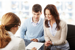 Young couple discussing financial plan with consultat. Contemporary young couple get financial advise Stock Photos