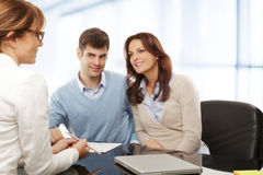 Young couple discussing financial plan with consultat. Contemporary young couple get financial advise Royalty Free Stock Image