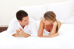 Young couple discussing lying on their bed Stock Photos