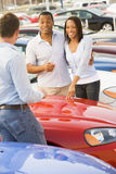 Young couple discussing new car with salesman. On lot Royalty Free Stock Photo