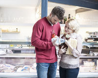 Young couple discussing over product outside cafe Royalty Free Stock Photo