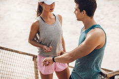 Young couple discussing training performance in break. Young couple discussing training performance during workout break outdoors. Runners with heart rate Royalty Free Stock Photo