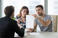 Young couple is dissatisfied with terms of contract. Young skeptic couple meet lawyer dissatisfied with terms of suspicious contract, refuse to sign. Family stock image