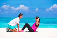 Young couple do abdominal crunches on white beach Stock Images