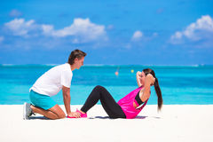 Young couple do abdominal crunches on white beach Royalty Free Stock Photography