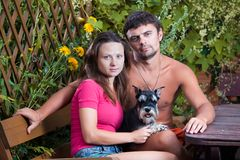 Young couple with a dog. Miniature schnauzer Royalty Free Stock Photography