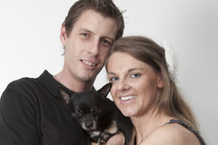 Young couple with dog. Young couple with Chihuahua dog against a white background Royalty Free Stock Photo