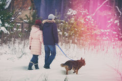 Young couple  with dog walking in the snowy village Royalty Free Stock Images