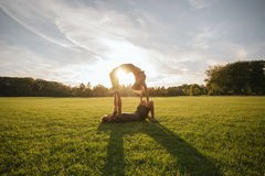 Young couple doing acrobatic yoga on lawn Royalty Free Stock Photo