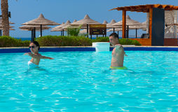 Young couple doing aqua fitness in swimming pool. At the hotel on a sunny summer day Stock Photography