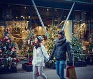 Christmas shopping in the city. Young couple doing christmas shopping in the city, smiling, walking hand in hand royalty free stock photography