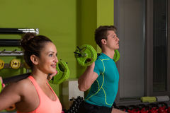 Young Couple Doing Exercise Barbell Squat Royalty Free Stock Photo