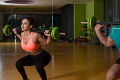 Young Couple Doing Exercise Barbell Squat Stock Images