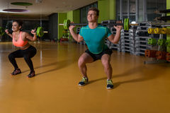 Young Couple Doing Exercise Barbell Squat Stock Photography