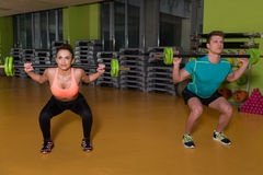 Young Couple Doing Exercise Barbell Squat Royalty Free Stock Images