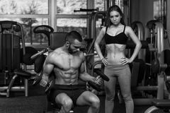 Young Couple Doing Exercise For Biceps With Dumbbells royalty free stock images