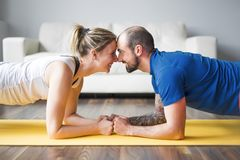 Young couple doing exercise at home in living room. A Young couple doing exercise at home in living room royalty free stock photo
