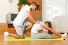 Young couple doing  exercises together. Young couple doing regular exercises  together on mat Royalty Free Stock Images