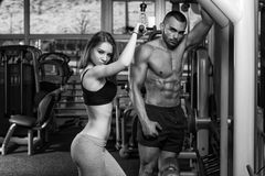 Young Couple Doing Heavy Weight Exercise For Triceps. Strong Young Couple Working Out On Machine For Triceps In The Gym With Exercise Equipment royalty free stock photos