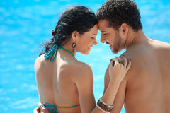 Young couple doing honeymoon in resort. Honeymoon: happy young newlyweds smiling and relaxing near hotel pool. Horizontal shape, rear view, copy space Royalty Free Stock Images
