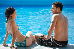 Young couple doing honeymoon in resort. Honeymoon: happy young newlyweds smiling and relaxing near hotel pool. Horizontal shape, rear view, copy space Royalty Free Stock Photos