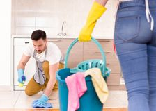 Young couple doing housework together. Mopping and cleaning floor in kitchen Royalty Free Stock Images