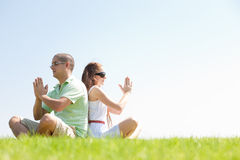 Young couple doing meditating. Young couple sitting on grass and doing meditating royalty free stock images