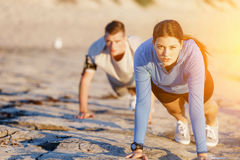 Young Couple Doing Push Ups On Ocean Beach Stock Photography