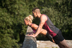 Young Couple Doing Push Ups Outdoor Stock Photo